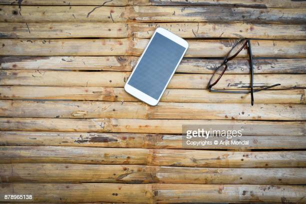 Top View of Isolated White Mobile Phone with Eye Glasses on Wooden Table