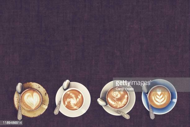 top view of latte art coffee mugs on timber background. - bovenkleding stockfoto's en -beelden