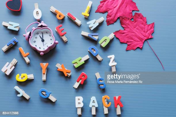 Top view of letters, word 'back' written with painted wood letters, alarm clock and atumn leaves on blue background.