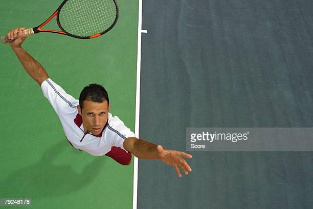 top view of male tennis player mid-serve - サーブを打つ ストックフォトと画像