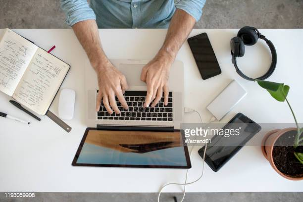 top view of man using laptop at desk in office - human body part stock-fotos und bilder