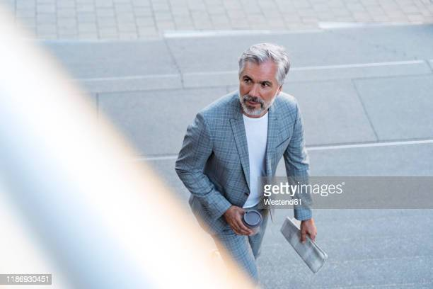 top view of mature businessman with newspaper and takeaway coffee - menswear stock pictures, royalty-free photos & images