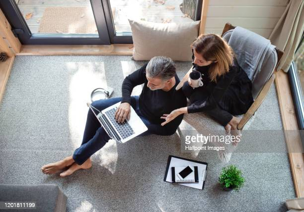 a top view of mature couple inside a tree house, using laptop. - simple living stock pictures, royalty-free photos & images