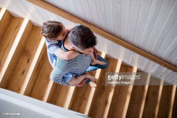 top view of mature father and small daughter indoors at home, walking down stairs. - staircase stock pictures, royalty-free photos & images