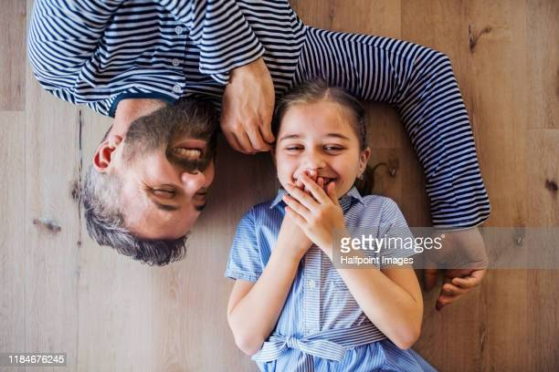 top view of mature father and small daughter lying on floor indoors at home. - human body part stock pictures, royalty-free photos & images