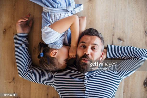 top view of mature father and small daughter lying on floor indoors at home, whispering. - whispering stock pictures, royalty-free photos & images