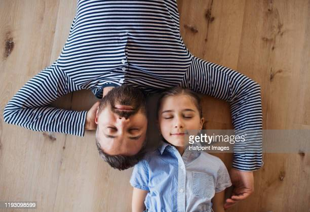 top view of mature father and small daughter lying on floor indoors at home. - lying down stock pictures, royalty-free photos & images