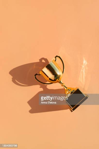 top view of metallic golden goblet on beige background with shadow. goal achievement concept - championship stock pictures, royalty-free photos & images