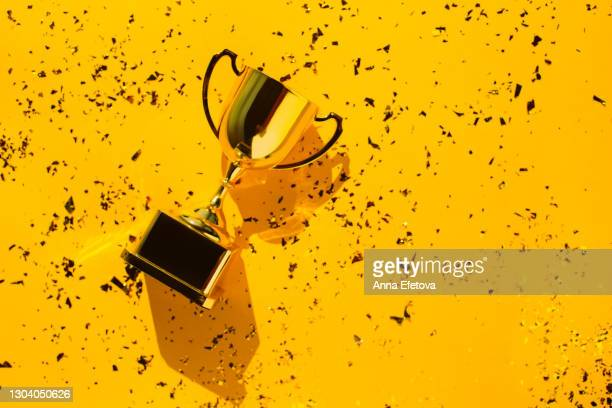 top view of metallic golden goblet on bright yellow background with sequin. goal achievement concept. trendy colors of the year - award stock pictures, royalty-free photos & images