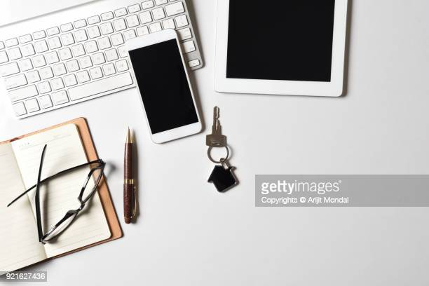 top view of modern property brokers work desk with smartphone, tablet, computer keyboard white background copy space - キーホルダー ストックフォトと画像