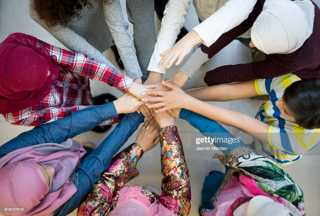 Top view of Muslim diverse friends in circle with hands together : Stock-Foto