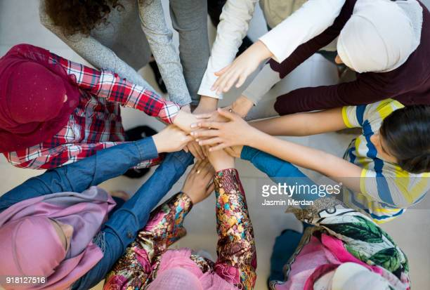 top view of muslim diverse friends in circle with hands together - us kultur stock-fotos und bilder
