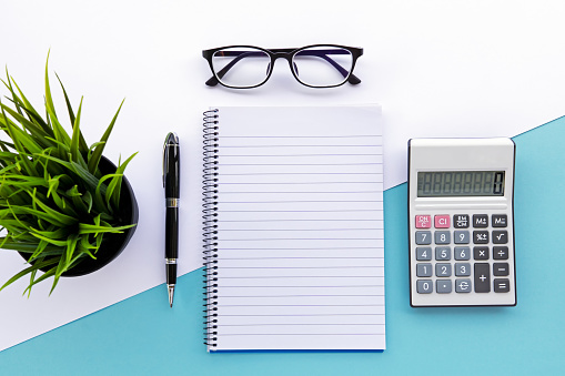 Top view of note pad, calculator, pen, eyeglasses and green plant - gettyimageskorea
