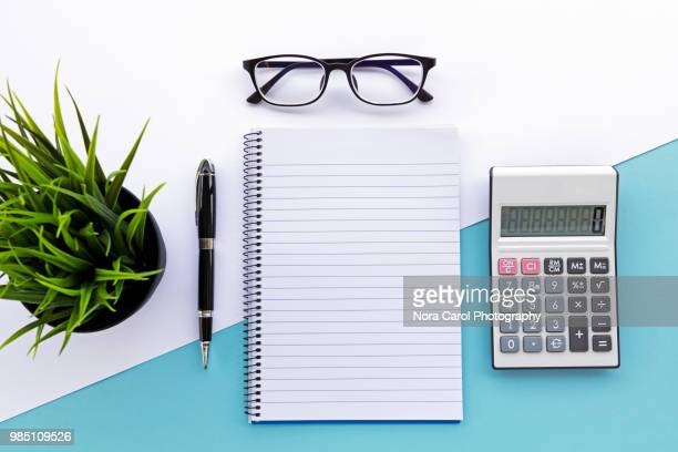 top view of note pad, calculator, pen, eyeglasses and green plant - personal accessory stock photos and pictures