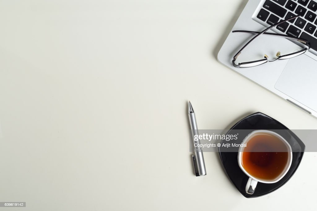 top office table cup. top view of office table with partial laptop keyboard, tea cup, pen, eye cup b