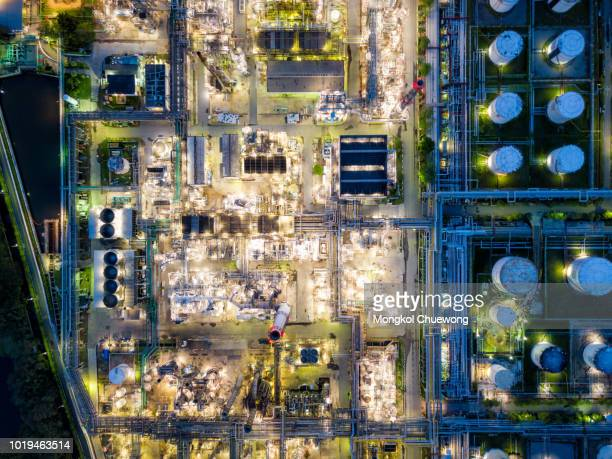 top view of oil refinery at night. aerial view of refinery plant at sunset. refinery factory and tank - top foto e immagini stock