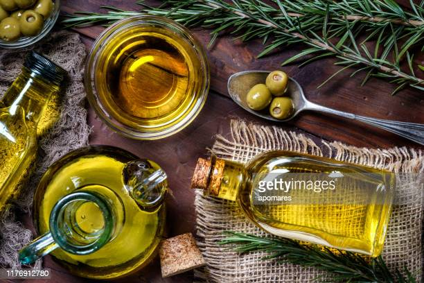 top view of olives and olive oil bottles on table in a rustic kitchen - olive oil stock pictures, royalty-free photos & images