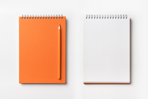 Top view of orange spiral notebook and color pencil collection 927623842
