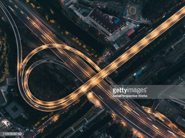 top view of overpass and city traffic at night - urban sprawl stock pictures, royalty-free photos & images