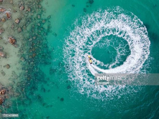 top view of people having fun on jetskipeople are playing a jet ski in the sea.aerial view. top view.amazing nature background.the color of the water and beautifully bright. fresh freedom. clear turquoise at tropical beach. - land vehicle stock pictures, royalty-free photos & images