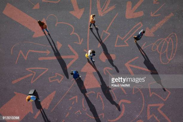 Top view of people walking around on painted asphalt with arrows