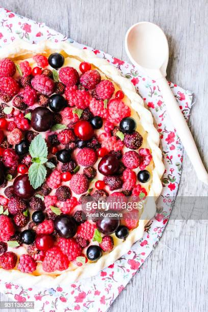 Top view of puff pastry sweet pizza pie with vanilla mascarpone cream cheese, raspberry, strawberry, black currant, cherry decorated with mint on a wooden table. Picnic food. Easter food.
