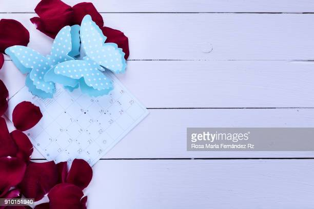 Top view of red rose petals framing February calendar sheet with two blue paper butterflies wooden background. Copy sace.