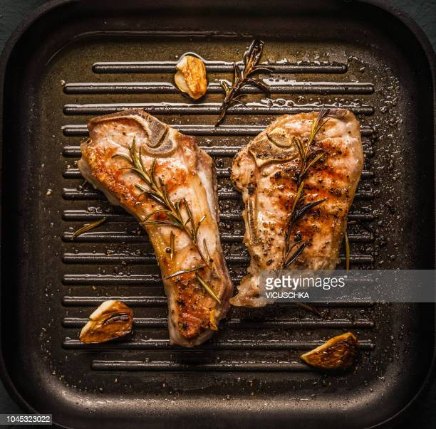 top view of roasted veal cutlet or ribeye steaks meat with flavors herbs - côtelette photos et images de collection