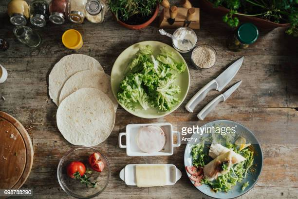 Top view of rustic wooden table with wrap sandwich