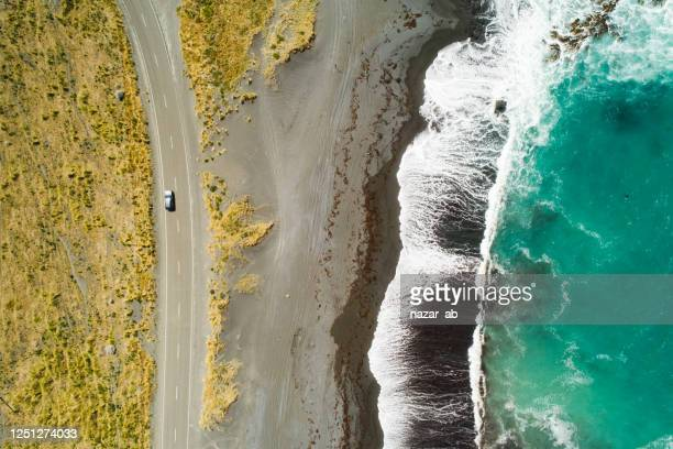 top view of sea, waves and road. - new zealand stock pictures, royalty-free photos & images