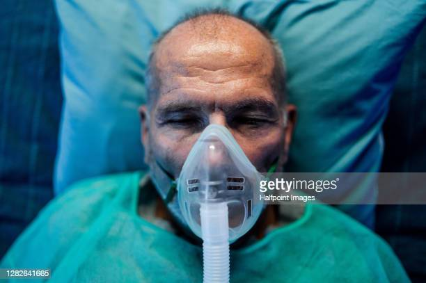 top view of senior covid-19 patient with oxygen mask in hospital, coronavirus concept. - oxygen mask stock pictures, royalty-free photos & images