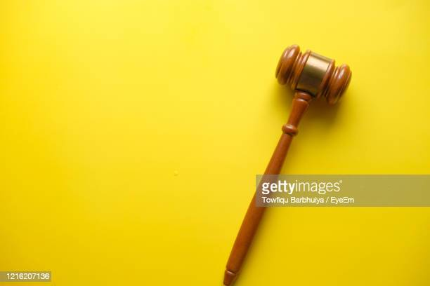 top view of single gavel on yellow background - gavel stock pictures, royalty-free photos & images