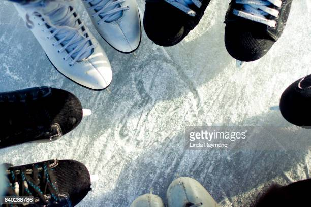 Top view of skates of boys and girls   on an outdoor skating rink around a heart shape drawn on ice