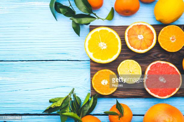 top view of sliced citrus fruits on blue wooden background - citrus fruit stock pictures, royalty-free photos & images