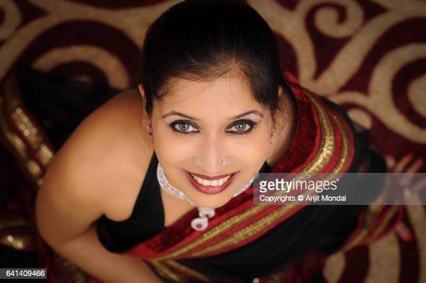 Top view of Smiling Indian woman looking at camera in black sari with diamond necklace