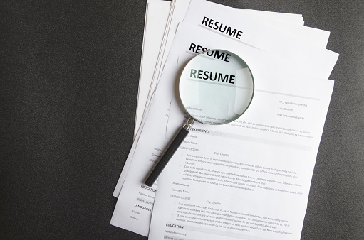 Top view of stack of resume files,magnifier on black surface.Concept of reviewing resume applictaions,searching for new employees 1138817616