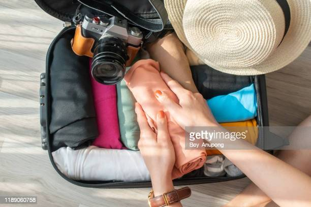 top view of tourist woman open suitcase for pack and arranging colorful cloths for travelling. - opgerold samenstelling stockfoto's en -beelden