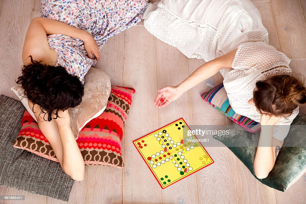 Top view of two best friends lying on the floor at home playing ludo : Stock Photo