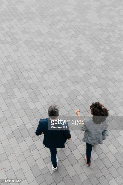 top view of two colleagues walking on a square - pavement stock pictures, royalty-free photos & images