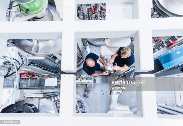 top view of two colleagues working at industrial robot in modern factory - automated stock pictures, royalty-free photos & images