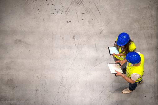 Top view of two construction workers wearing hardhats and reflective jackets holding tablet and checklist on gray concrete background. Group of engineers sharing ideas about the project. 1140820186