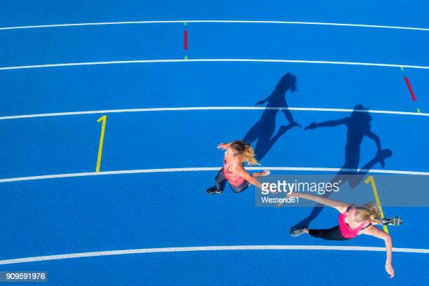 Top view of two female runners passing the baton on tartan track
