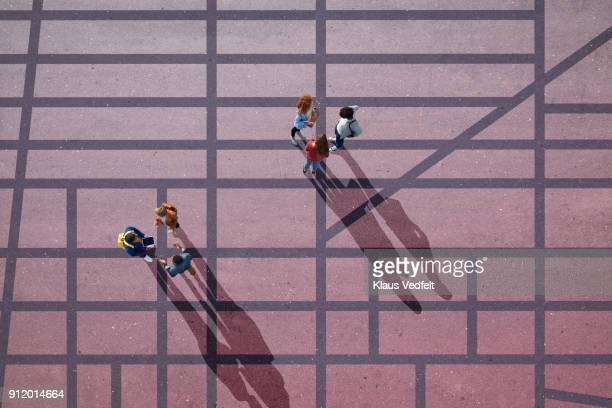 Top view of two groups of people, standing on city roadmap, painted on asphalt