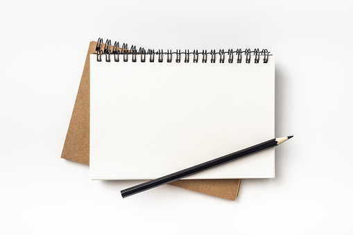 Top view of two kraft spiral notebook and black pencil 924460588