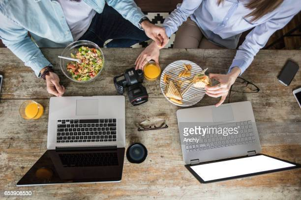 Top view of two people eating near the laptops