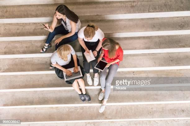 draufsicht des urbanen menschen halten technologien beim sitzen auf den stufen - campus stock-fotos und bilder