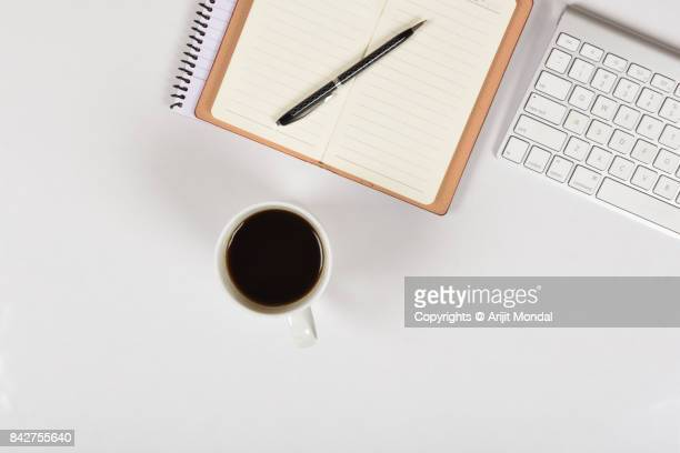Top view of white desktop background with notebook, coffee, computer keyboard copy space