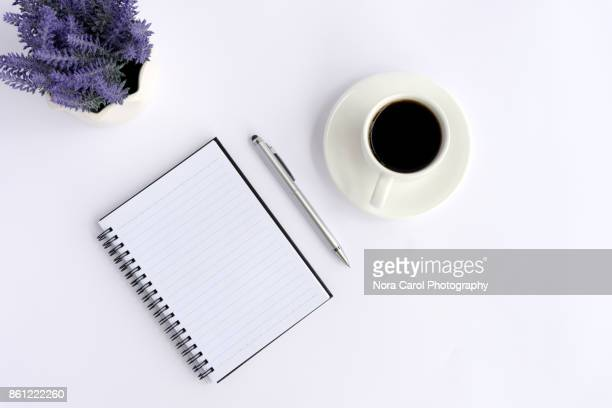 Top View of White Office Desk With Note Pad, Pen, Flower And Coffee