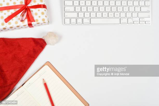 Top view of white office table with cropped computer keyboard, Christmas theme items flay lay