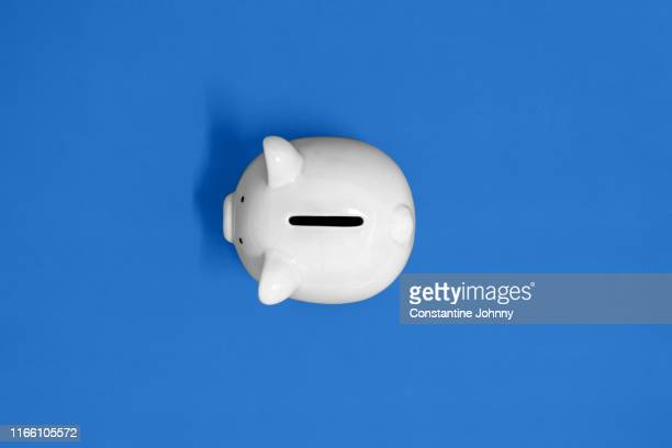 top view of white piggy bank on yellow background - piggy bank stock pictures, royalty-free photos & images